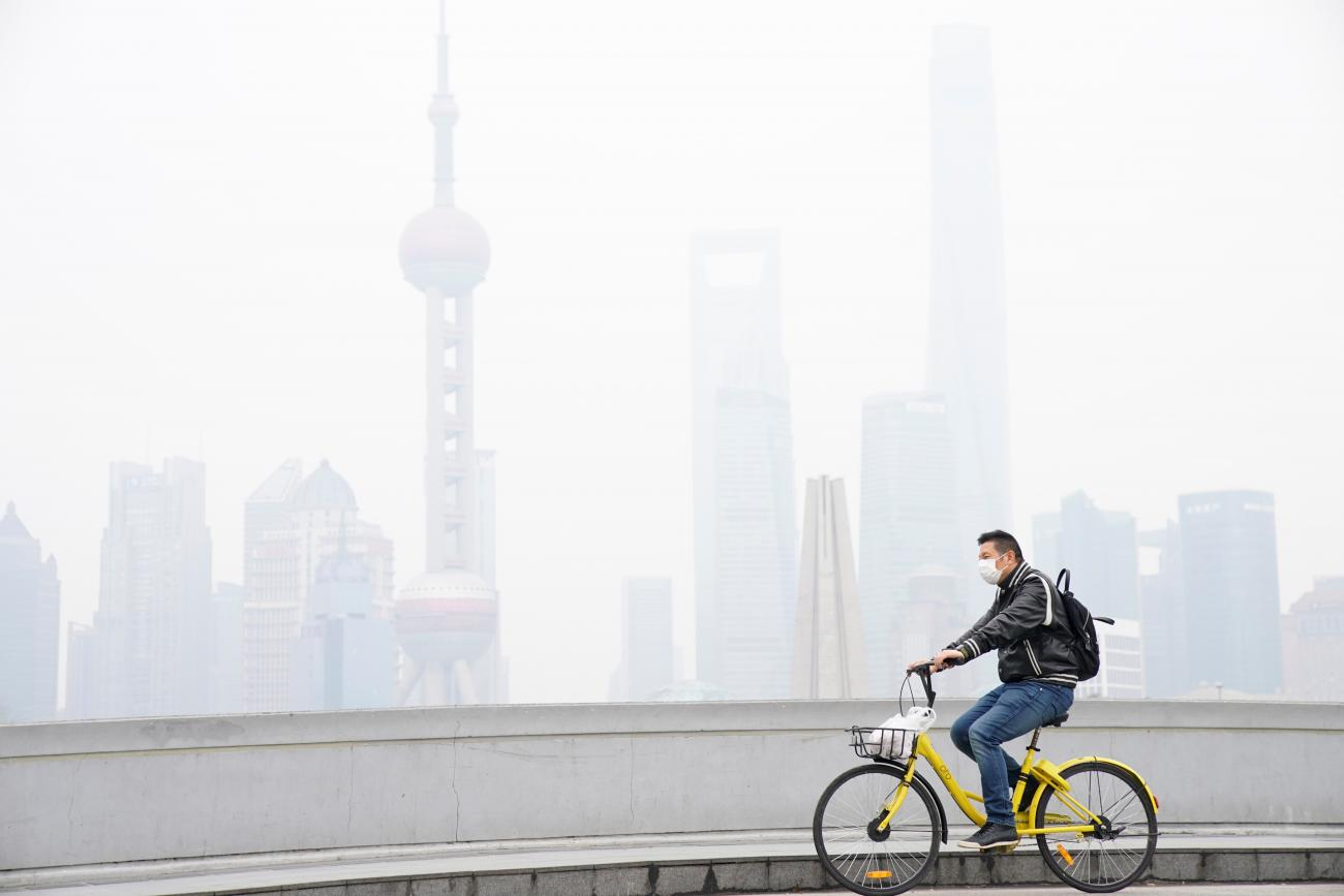A man wearing a face mask rides a bicycle on a bridge in front of the financial district of Pudong covered in smog during a polluted day in Shanghai, China on November 22, 2017.