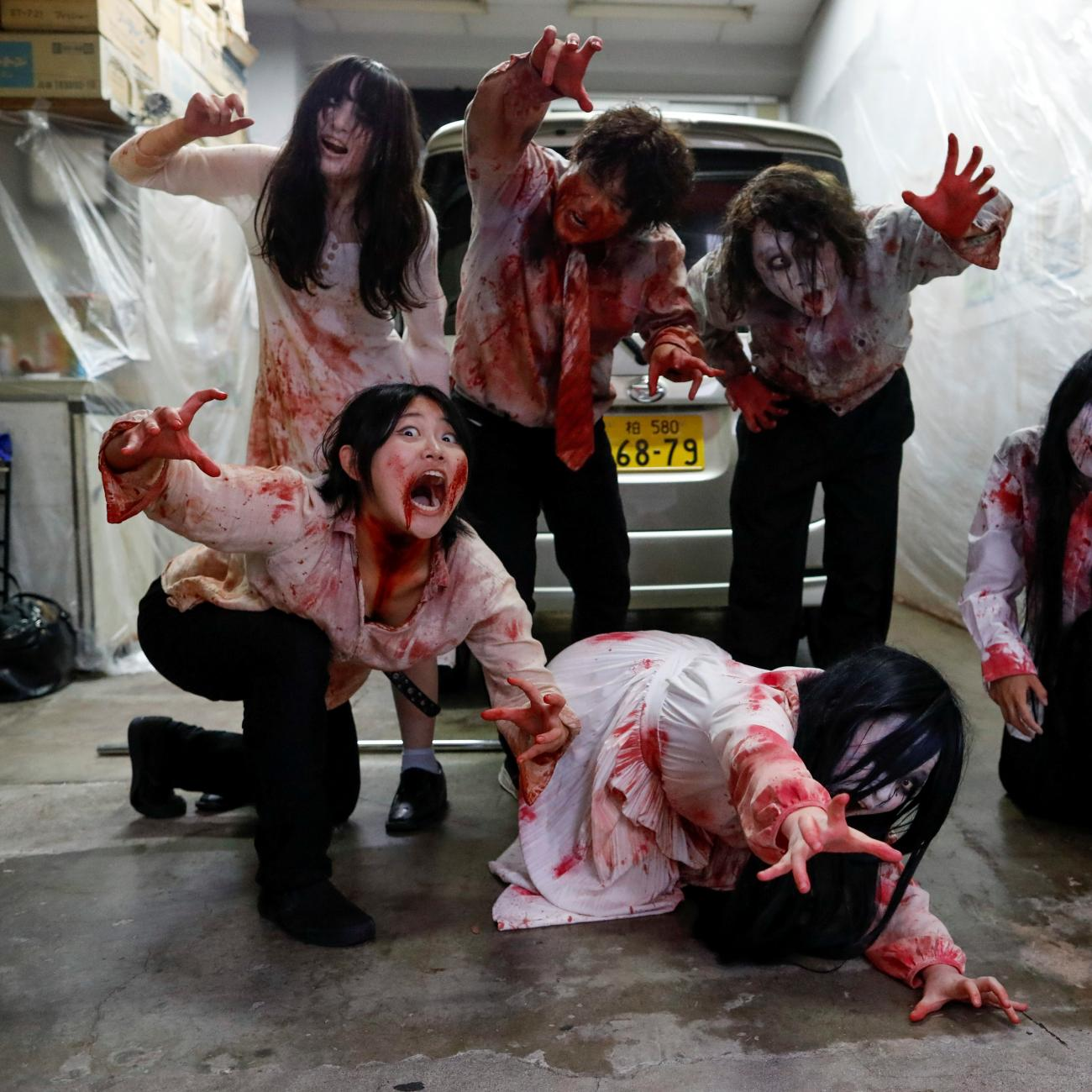 Actors dressed as zombies or ghouls pose for a photograph before their performance at a drive-in haunted house show by Kowagarasetai (Scare Squad), for people inside a car in order to maintain social distancing amid the spread of the coronavirus disease (COVID-19), at a garage in Tokyo, Japan July 3, 2020.