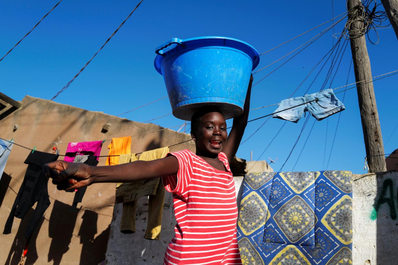 A girl carries a bucket with laundry on her head while heading home as the spread of the coronavirus disease continues, in Yoff neighbourhood, Dakar, Senegal on January 26, 2021.