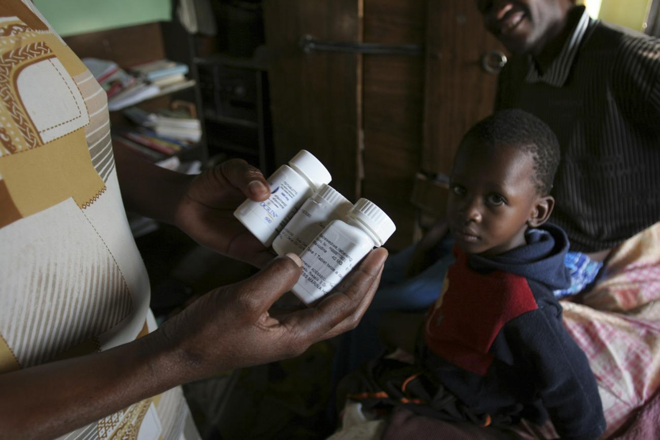 A woman holds bottles of daily anti-retroviral drugs and vitamin supplements as her husband and son look on in their one-room home on the outskirts of Botswana'a capital Gaborone, on November 27, 2006.