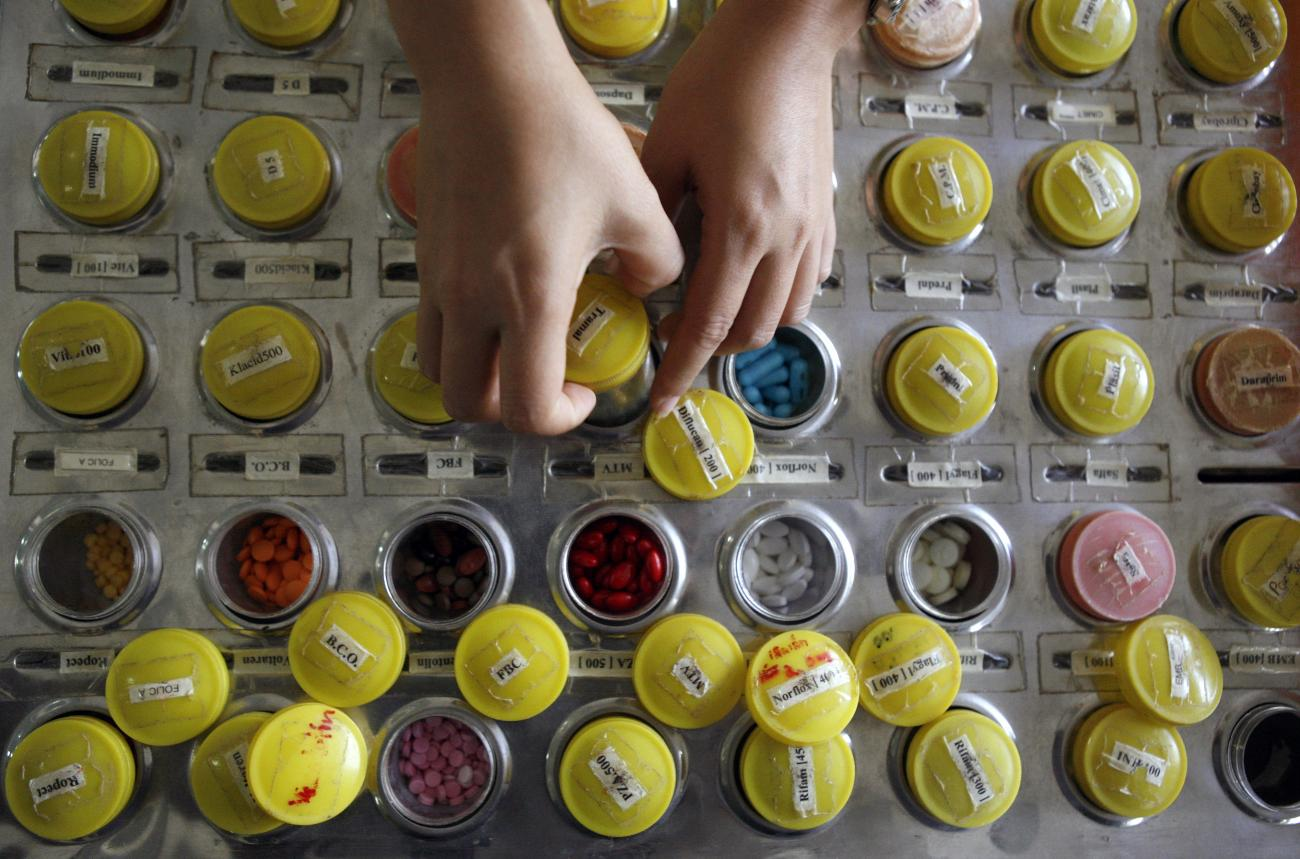 A nurse prepares doses of brand name and generic HIV-AIDS drugs for patients at the Phrabat Nampu Temple in Thailand's Lopburi Province February 17, 2007.
