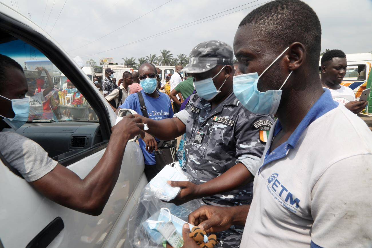 A road safety officer distributes face masks during an awareness campaign organized by the Ministry of Transport at Yopougon station in Abidjan, Ivory Coast on January 19, 2021.
