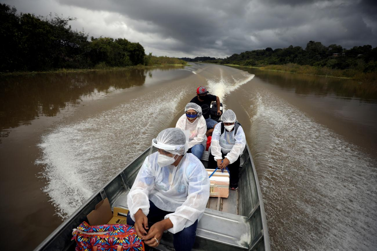 Municipal health workers travel on a boat along the Solimoes river banks to administer the Oxford-AstraZeneca coronavirus vaccine in Manacapuru, Amazonas state, Brazil on February 1, 2021.