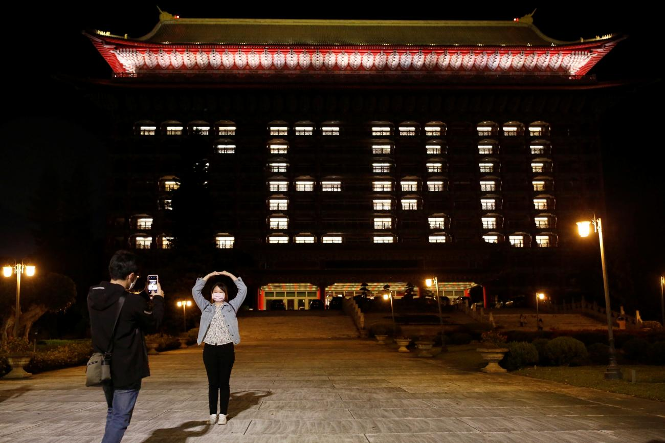 People wearing a face masks pose in front of the Grand Hotel that's using hotel room lights to celebrate zero confirmed cases in Taipei, Taiwan on April 16, 2020.