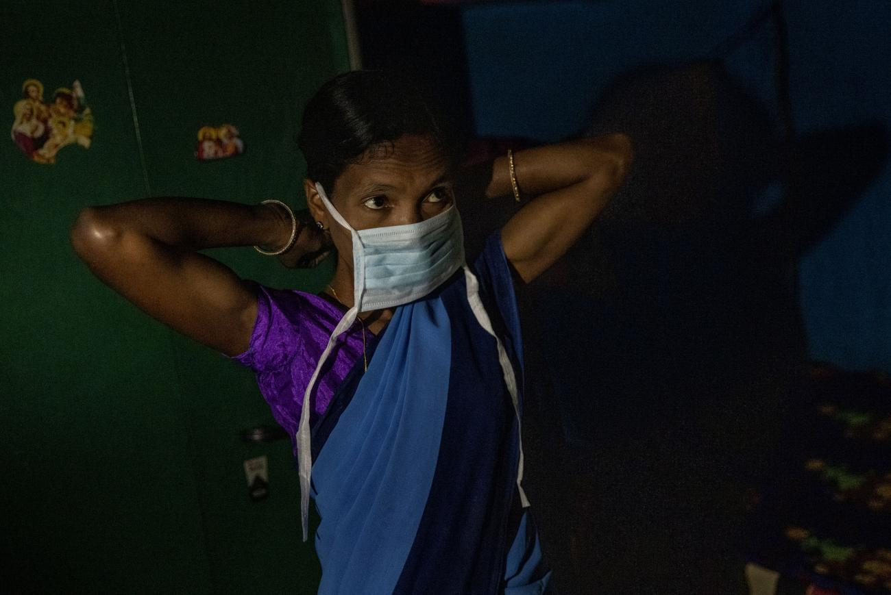 A health worker, puts on a protective face mask as she gets ready to receive the Oxford/AstraZeneca coronavirus vaccine in Pendajam village in Koraput, India, January 16, 2021.