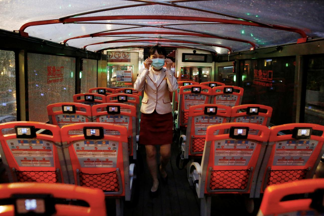 A tour guide adjust her face mask to protect herself from the coronavirus disease (COVID-19) in an empty Taipei Sightseeing bus in Taipei, Taiwan, May 22, 2020.