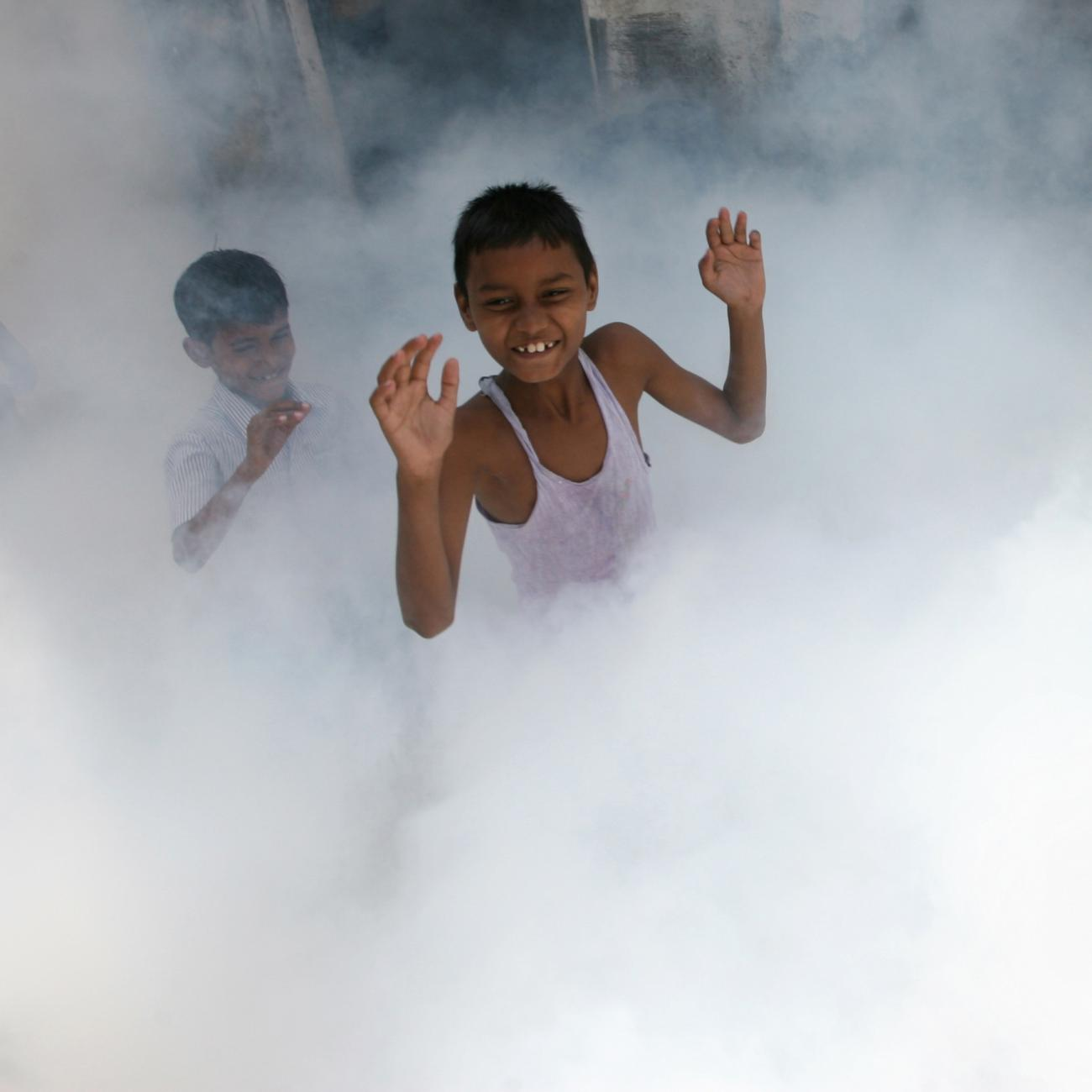 Children play as a health worker fumigates a residential area, where cases of malaria were reported, in Mumbai March 20, 2009.