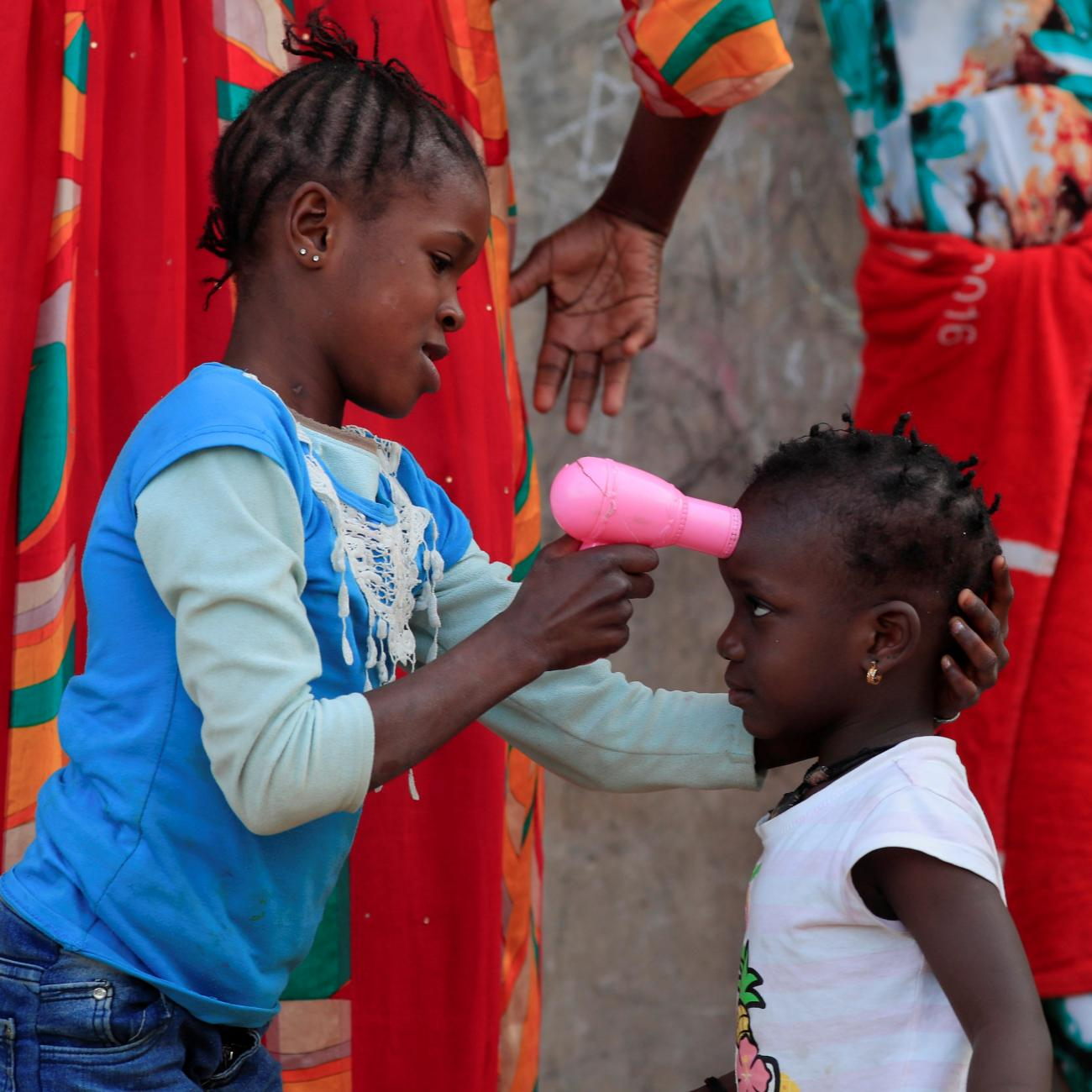 A girl uses a toy hairdryer as an infra-red thermometer on her friend as they play at Hann Bay on the eastern edge of Dakar, Senegal, April 12, 2021