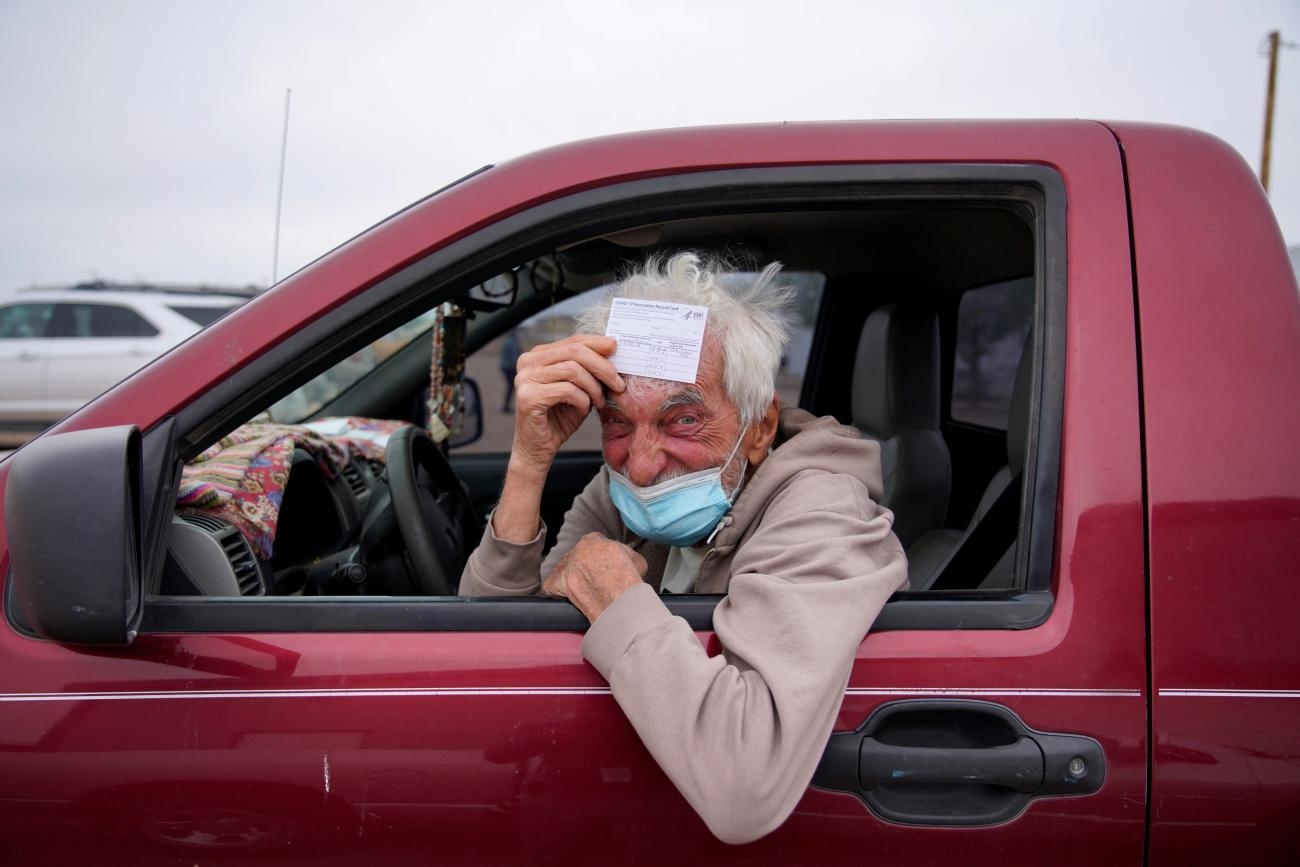 poses for a portrait with his vaccination card after receiving his coronavirus disease (COVID-19) vaccine at a rural vaccination site in Columbus, New Mexico, U.S., April 16, 2021.