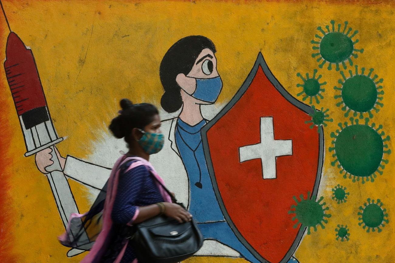 A woman walks past a graffiti on a street, amidst the spread of the coronavirus disease (COVID-19) in Mumbai, India, May 10, 2021.