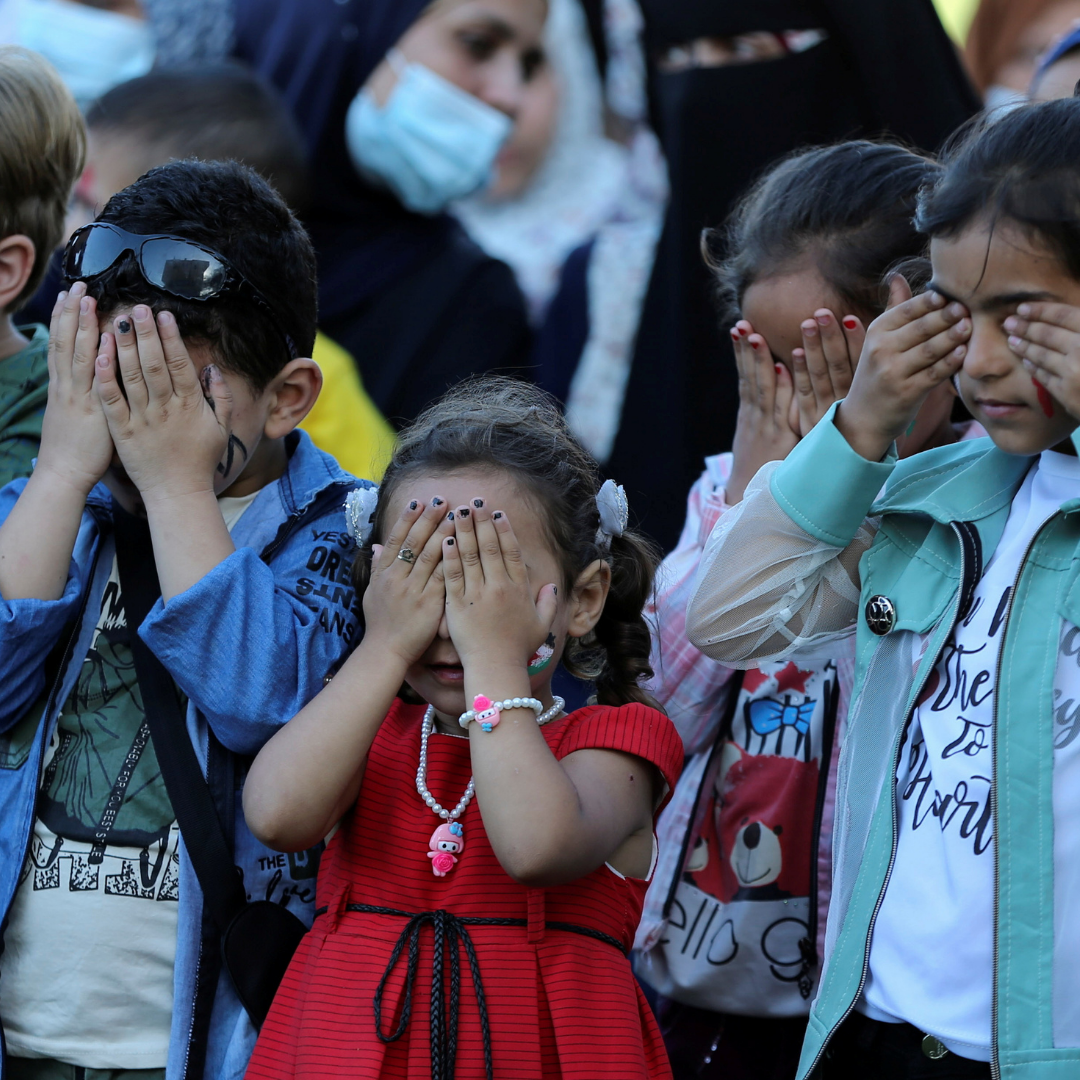Palestinian children cover their eyes as they participate in a mental health support session in Khan Younis in the southern Gaza Strip on June 6, 2021.