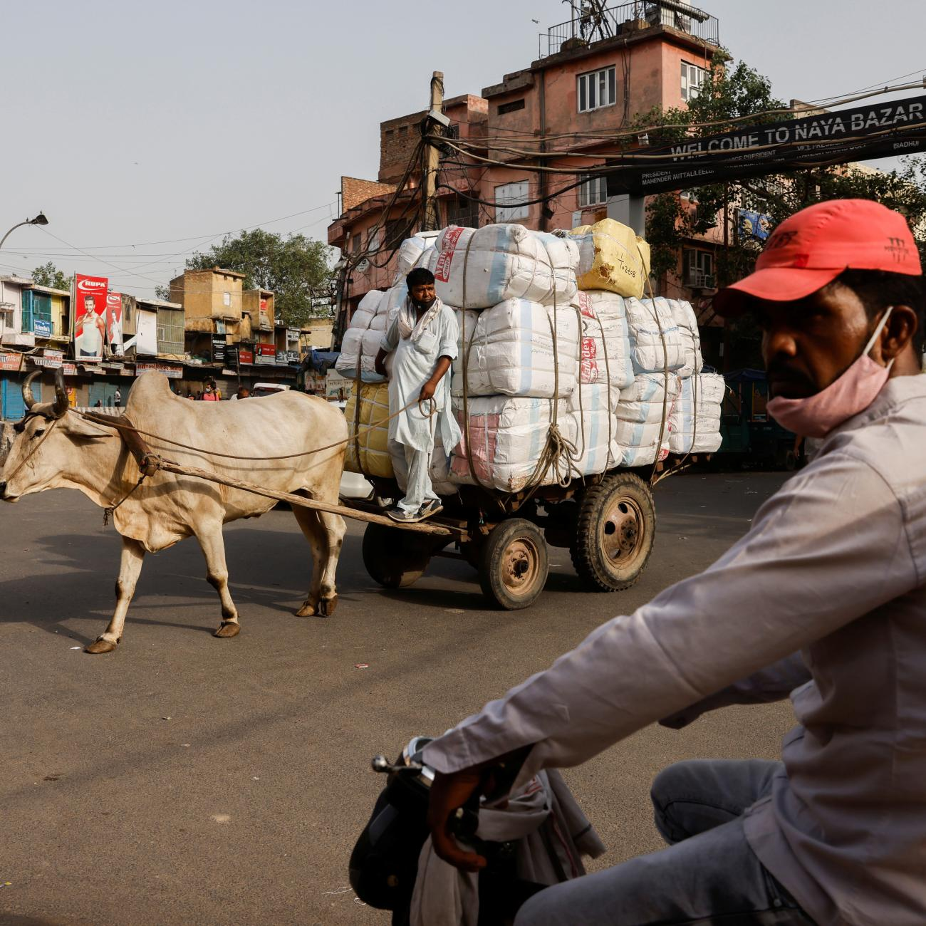 A man rides a motorcycle in front of a worker transporting sacks of spices loaded on a bullock cart at a wholesale market in the old quarters of Delhi, India.