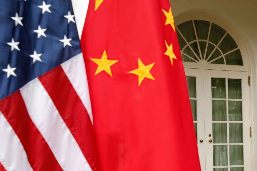 A close-up photo of the U.S. and Chinese flags hanging gently from poles at the White House in 2015.