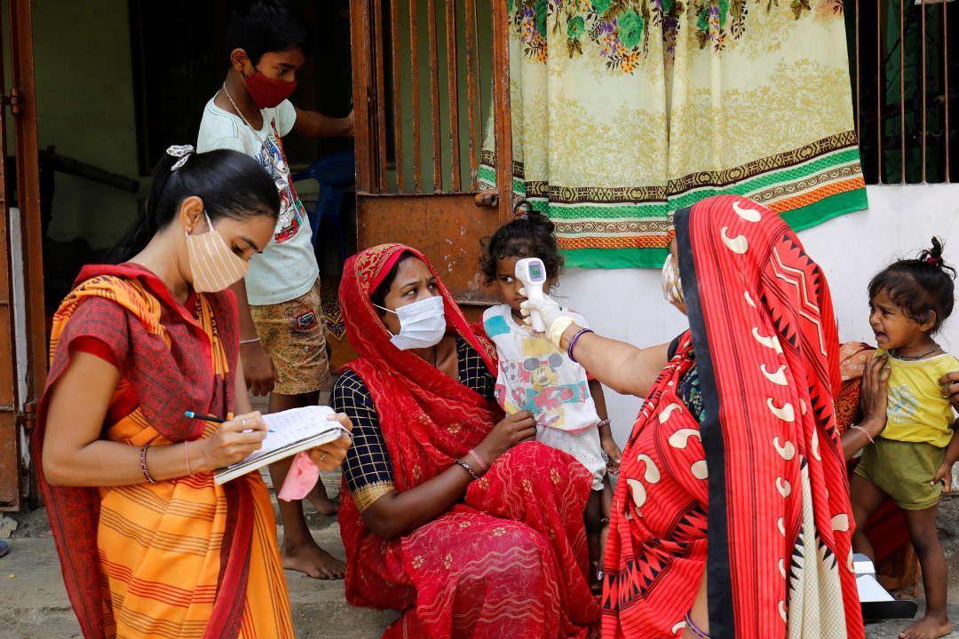 A health-care worker checks the temperature of a child as other adults and children watch during a door-to-door COVID-19 surveillance visit in a village on the outskirts of Ahmedabad, India on June 9, 2021.