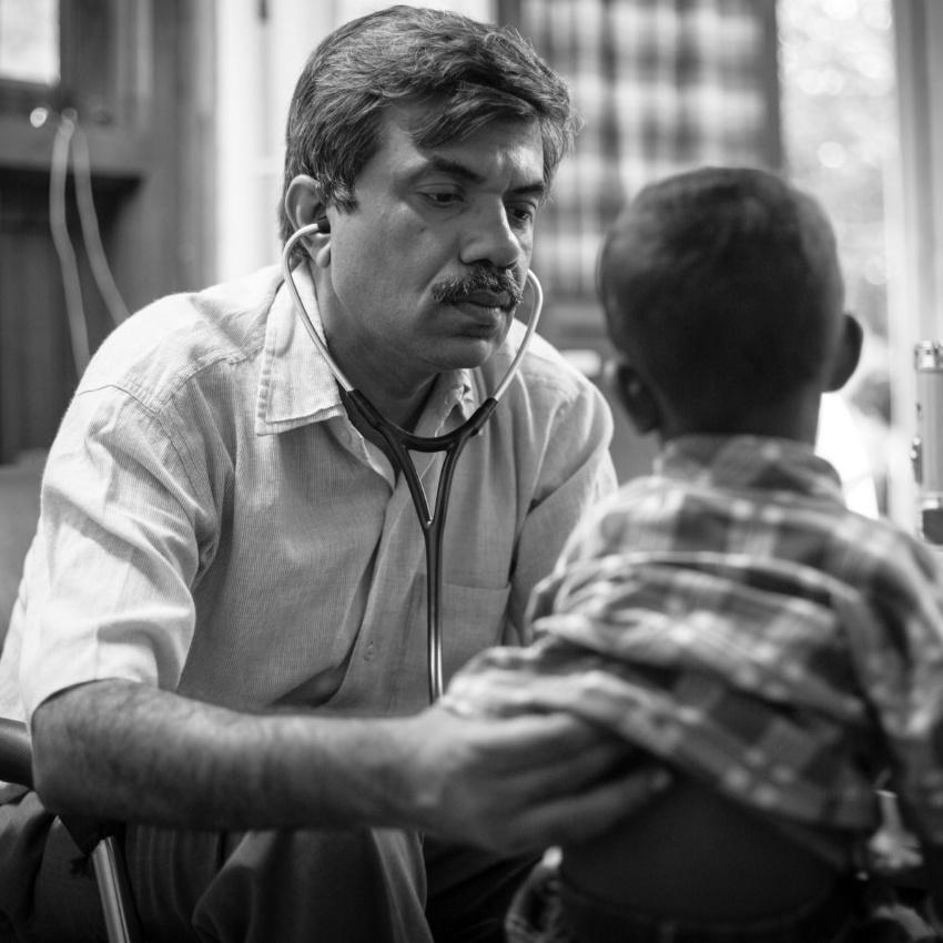 Dr. Yogesh Jain examines a young boy who has sickle cell disease for pneumonia, located in a remote village clinic that does not have any x-ray facilities, in May 2017 at  Jan Swasthya Sahyog community health program