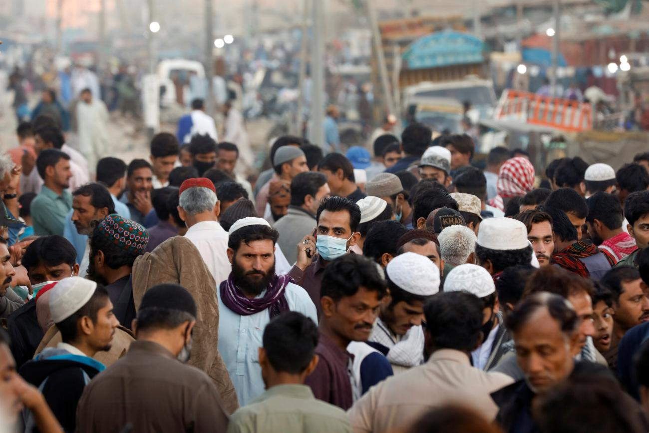 A man wearing a protective mask walks through a crowd of people along a makeshift market as the outbreak of the coronavirus disease (COVID-19) continues, in Karachi, Pakistan January 17, 2021