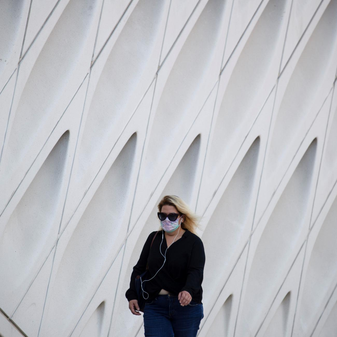 A woman wearing a face mask walks by The Broad Museum in downtown during the outbreak of the coronavirus disease (COVID-19), in Los Angeles, California, U.S., August 13, 2020.