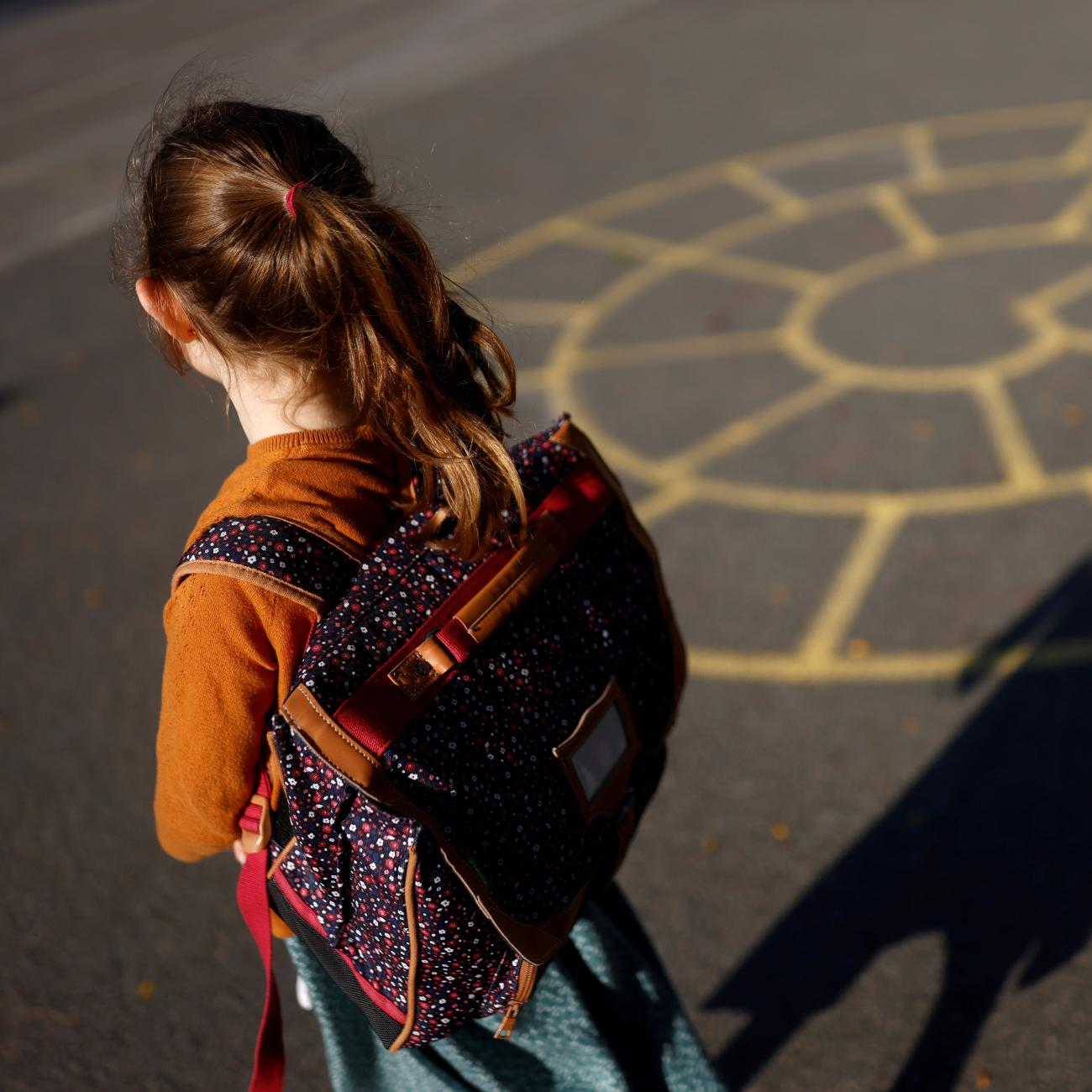 A child arrives at a primary school on the first day of the new school year after summer break in Vertou, France, on September 2, 2021.