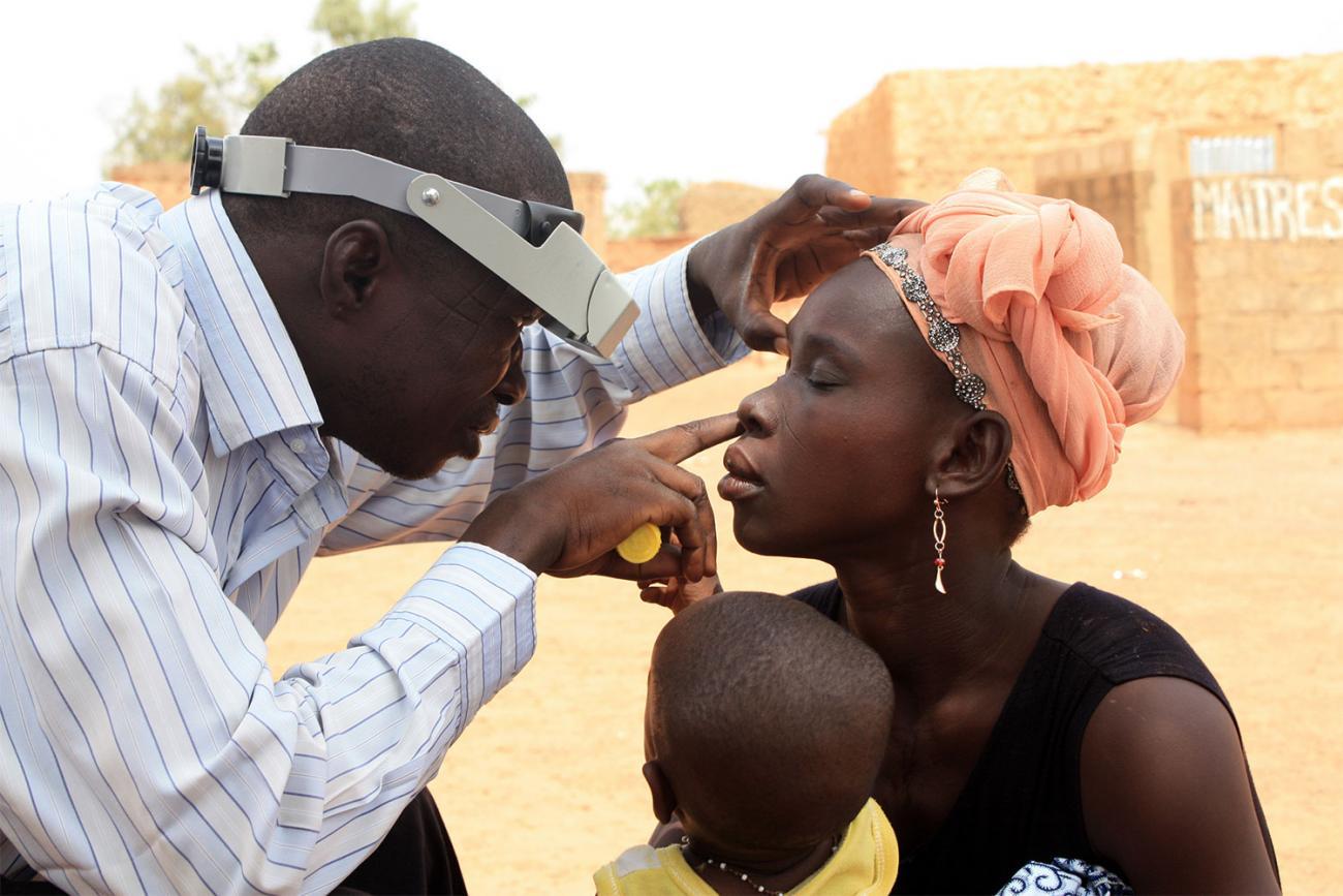 Technician doing eye exam during azithromycin mass drug administration training exercise near Ouagadougou, Burkina Faso.