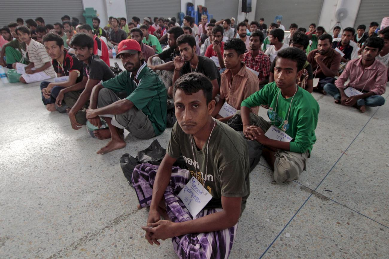 Migrants from Myanmar and Bangladesh in Thailand's southern Songkhla province on May 9, 2015. In 2001 Thailand launched a health insurance scheme for migrants and expanded it to dependents in 2005. Picture shows a triangle of men sitting cross-legged looking at the camera. REUTERS/Surapan Boonthanom.