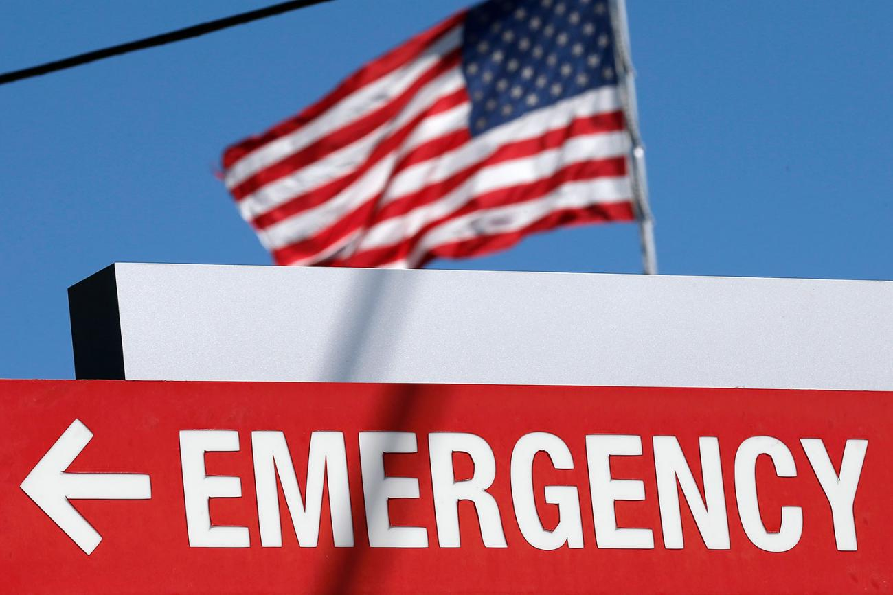 """An entrance sign to the Texas Health Presbyterian Hospital in Dallas, Texas, on October 4, 2014. The sign says """"EMERGENCY"""" and points to the left. In the background we can see an American flag billowing against a brilliant clear blue sky. REUTERS/Jim Young"""