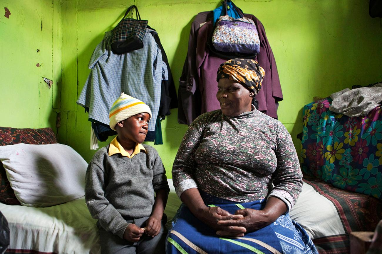 Two ends of the age spectrum: Thenjiwe Madzinga, 66, and grandson Thina Gxotelwa in a small room they share in Cape Town's Khayelitsha township on Feb. 23, 2010. Madzinga cares for five grandchildren. Picture shows the pair sitting on a bed in a small room with bright green walls. She is looking lovingly at him, and he is looking at her and smiling, perhaps embarrassed at the camera. REUTERS/Finbarr O'Reilly
