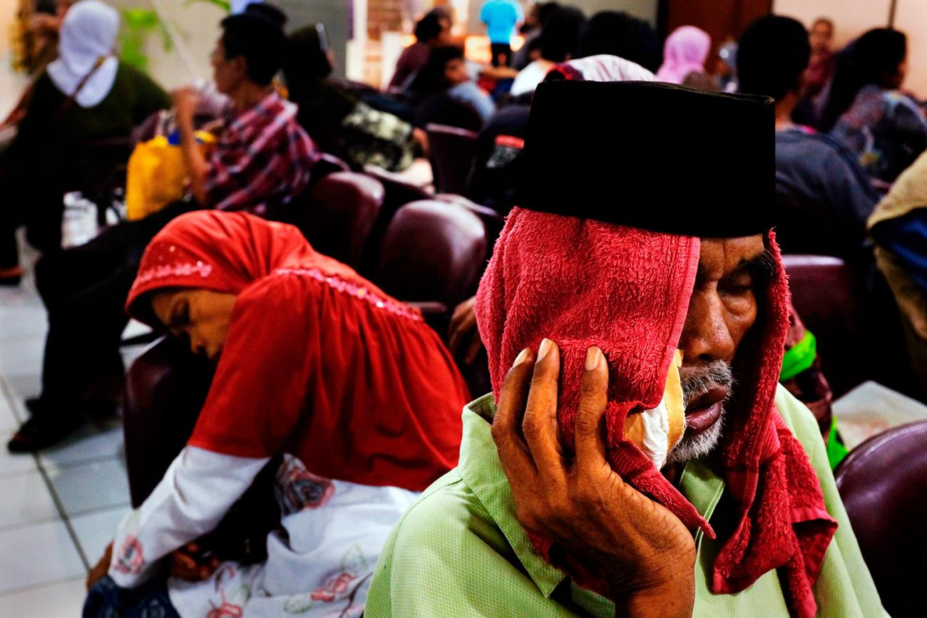 People waiting at Fatmawati hospital in Jakarta on May 17, 2013, after Indonesia announced plans to implement nationwide health care, with the aim to covering all Indonesians by the end of the decade. The picture shows a crowded waiting room with a man in the foreground with a red cloth draped over his head and holding what appears to be a bag of ice against his cheek. He looks like he is suffering. REUTERS/Beawiharta.