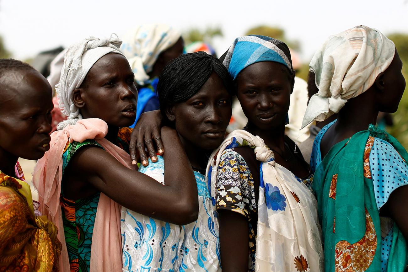 Women wait in line during a UNICEF supported mobile health clinic in the village of Rubkuai in Unity State, South Sudan on February 16, 2017. Picture shows five women in a line with more lined up on the other side of them. The three women in the middle are standing very close, and the third has her arms around the shoulders of the second, suggesting they all know each other. This photo is moving in its simple, straightforward humanity. REUTERS/Siegfried Modola