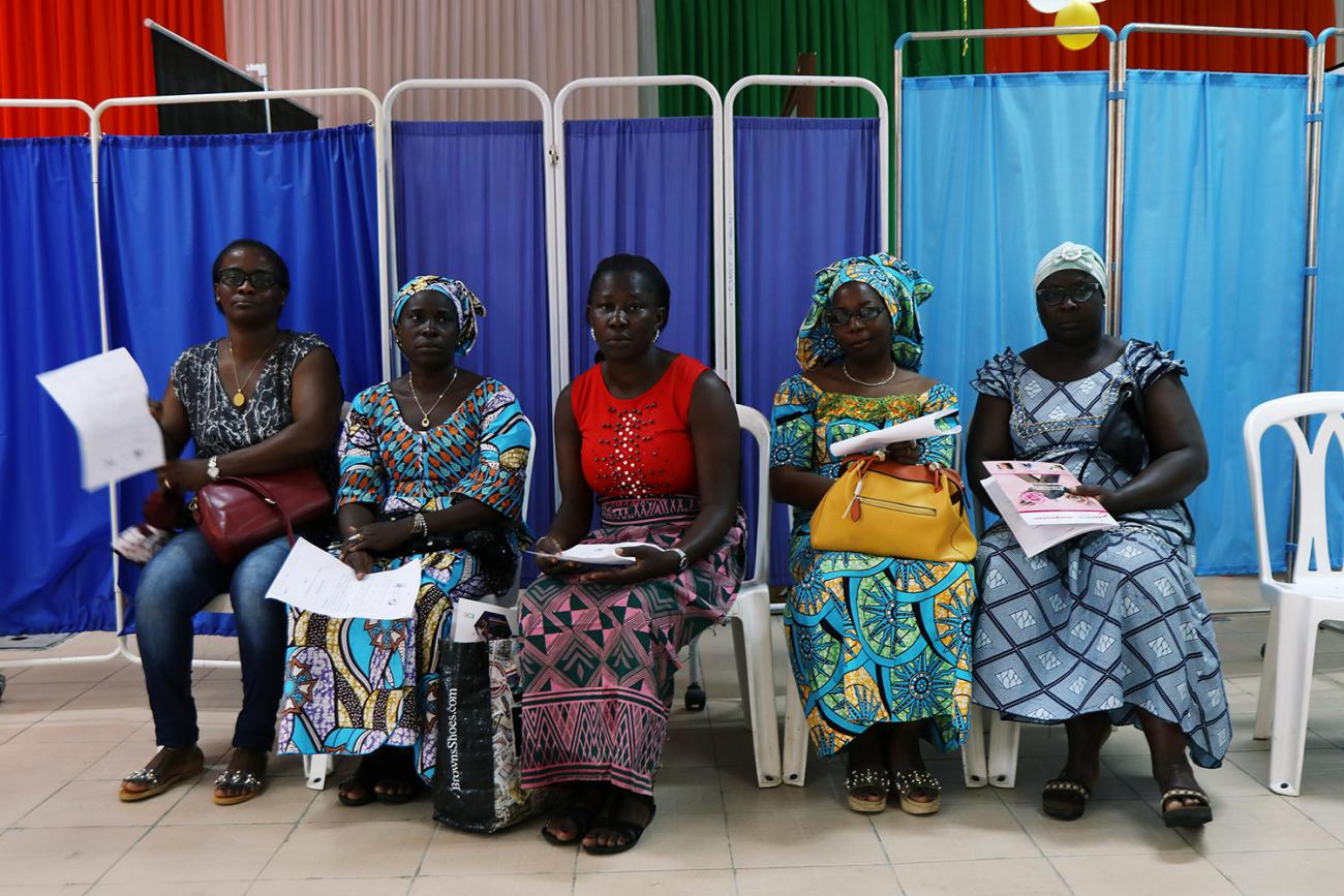 Women sit as they prepare for screenings during the breast cancer prevention campaign in Abidjan, Ivory Coast on October 12, 2019. Image shows a row of several women wearing colorful clothes. REUTERS/Luc Gnago
