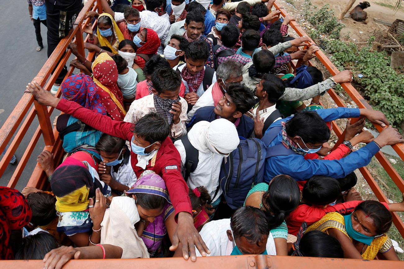 India migrant workers and their families in Ahmedabad board a truck to return to their villages on March 25, 2020 after India ordered a 21-day nationwide lockdown to limit the spread of coronavirus. The photo shows the back of a flatbed truck from above. People are packed in the vehicle beyond capacity, sardined together for what looks like a bumpy ride. REUTERS/Amit Dave
