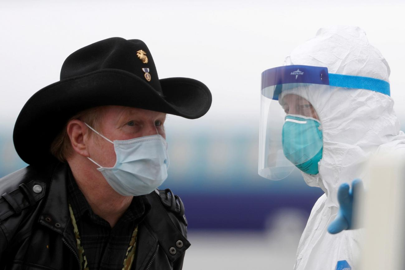 A worker in protective gear directs a masked passenger disembarking from the cruise ship Grand Princess in Oakland, California on March 10, 2020 amid concern over the growing COVID-19 pandemic. The picture shows a man wearing a mask and a cowboy hat standing facing a health worker in full protective gear. REUTERS/Stephen Lam