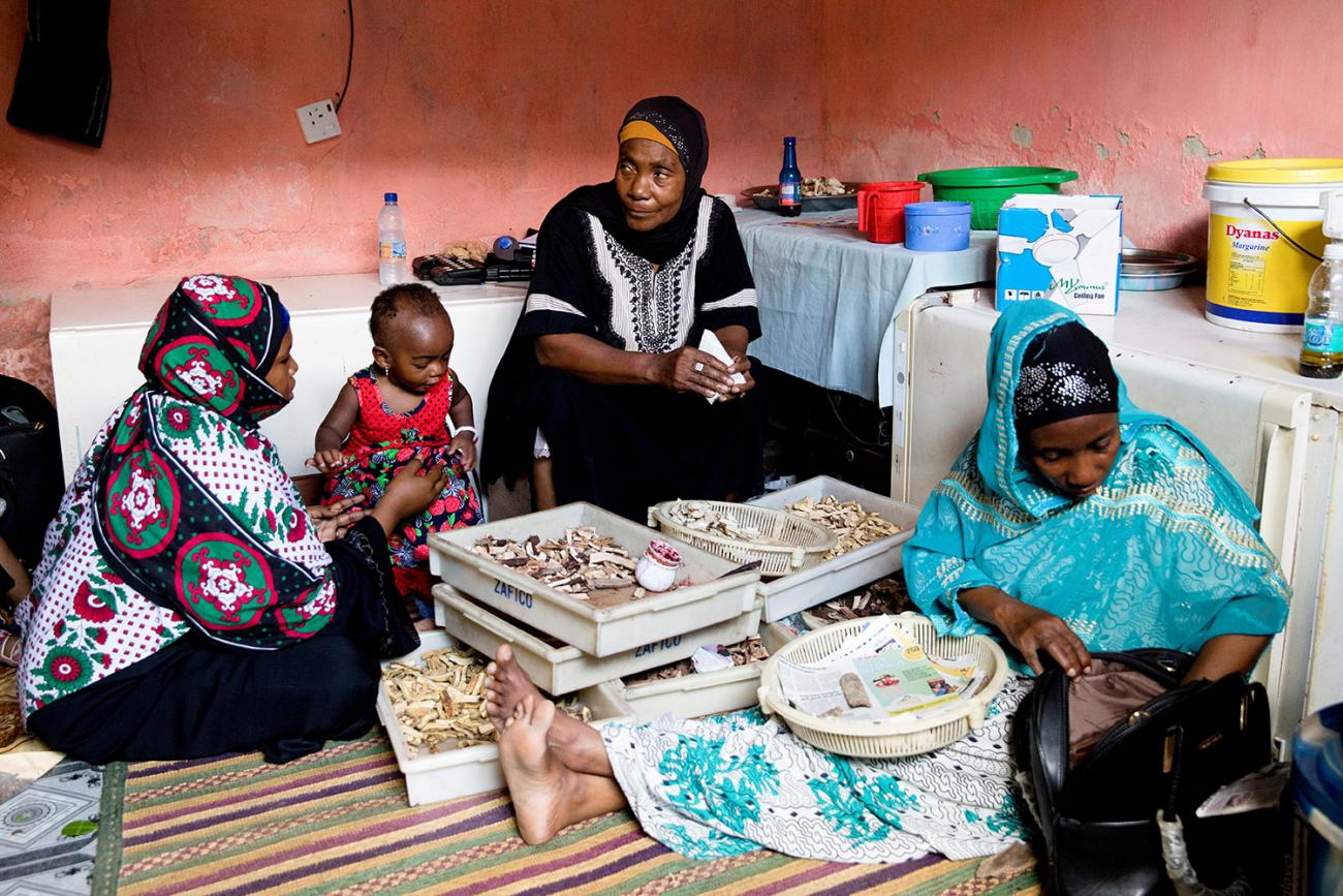 Traditional healer Bi Mwanahija Mzee folds root medicine in a piece of paper to give to a mother who complains of her child's constipation in Zanzibar City, Tanzania on January 31, 2019. The photo shows the healer facing the camera and sitting between two other women and a child. REUTERS/Nicky Woo