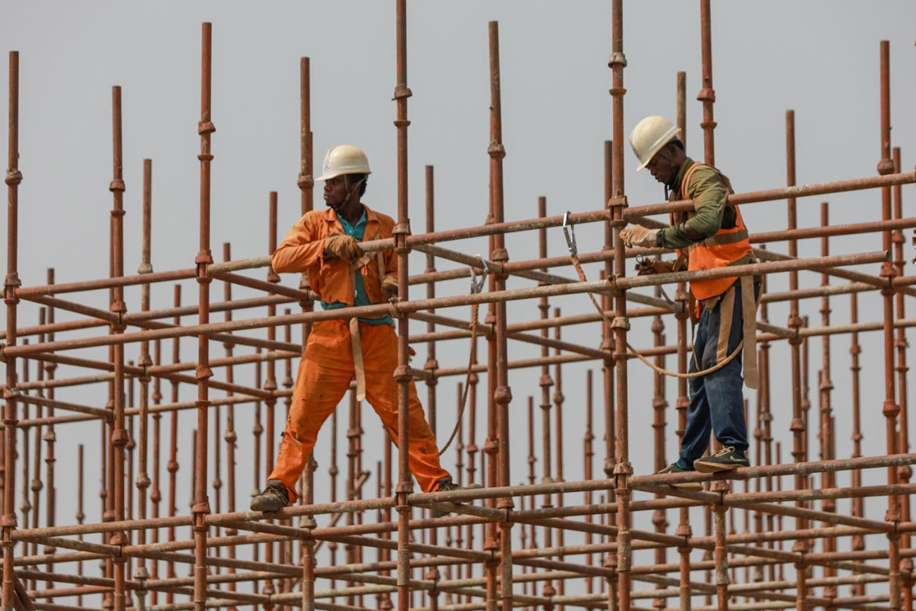 Construction workers stand on a scaffolding on February 18, 2020 in Abuja, Nigeria—one of the countries with a looming crisis of an unmet need for housing coupled with a projected population increase. Picture shows a man in a bright orange jump suit and a yellow contruction hat balancing with his legs wide apart on a metal scaffolding against a grey sky. REUTERS/Afolabi Sotunde