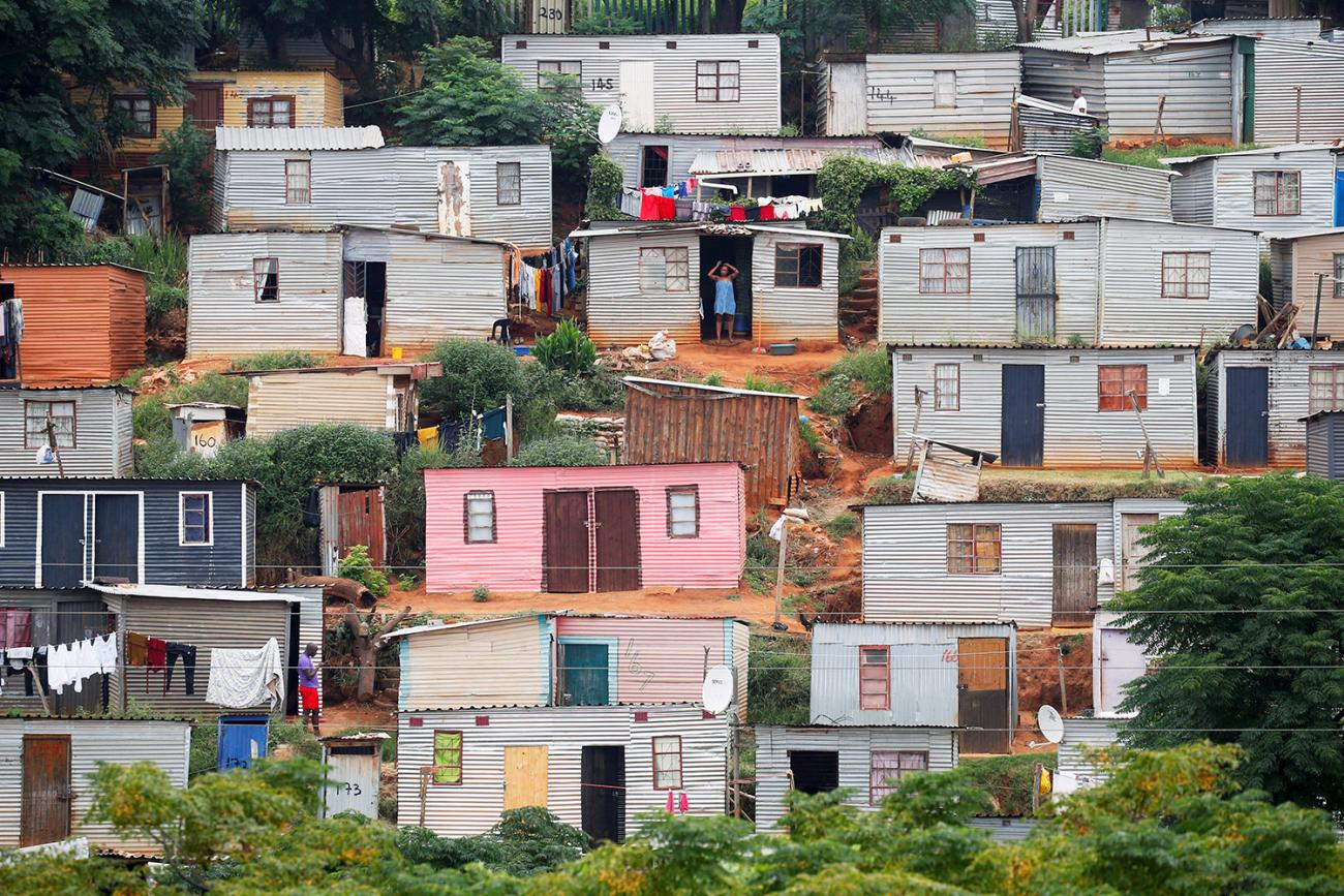 A general view of shacks during a nationwide twenty-one day pandemic lockdown in an attempt to contain coronavirus infections in Umlazi township near Durban, South Africa, on March 31, 2020. The photo shows a hillside covered with tin shacks, some colorfully painted. REUTERS/Rogan Ward