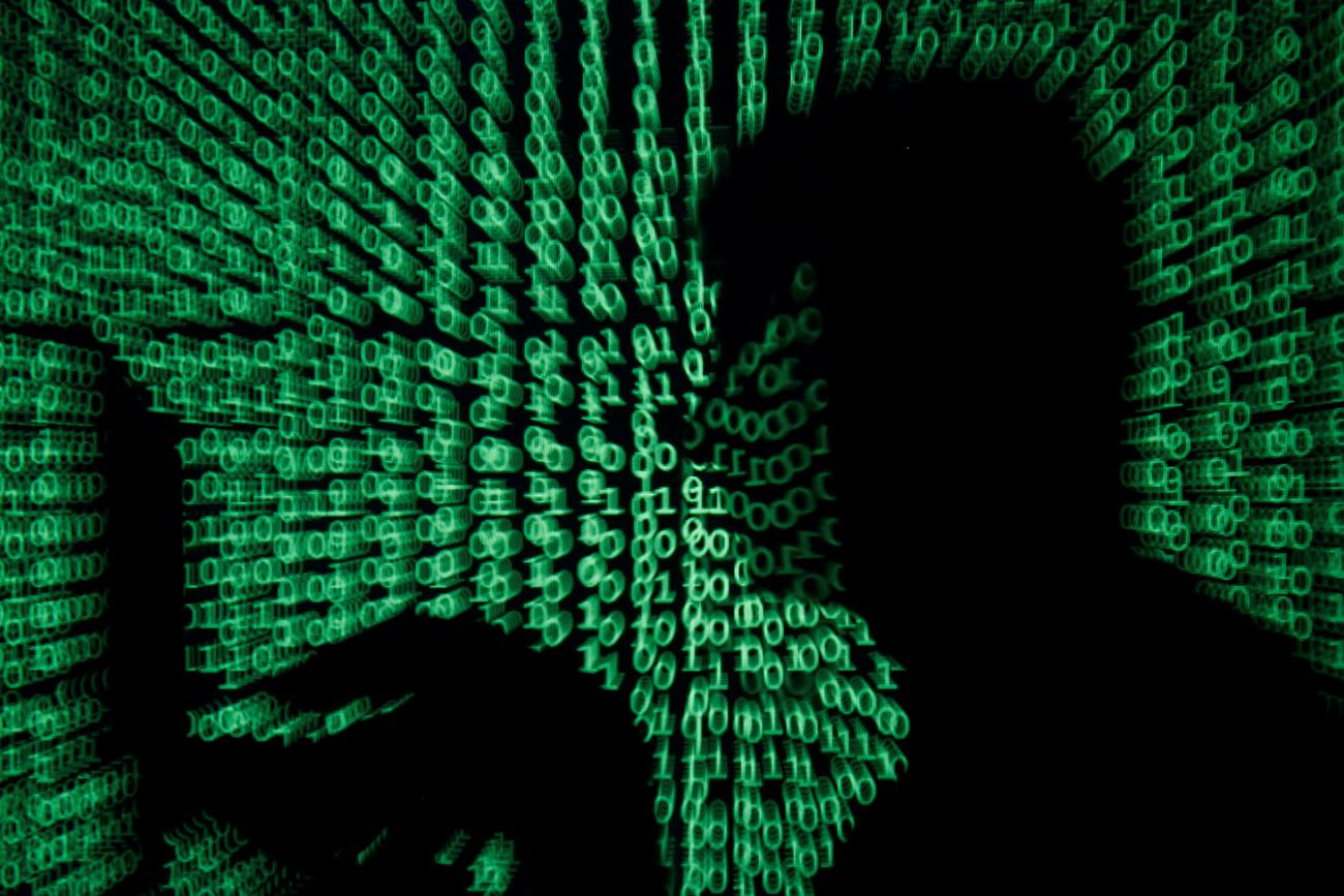 """We are facing a digital moment of truth as a result of the new coronavirus. A man holds a laptop computer as cyber code is projected on him in this illustration and picture produced on May 13, 2017. the image shows the silhouette of a man on a laptop with green ones and zeroes, reminiscent of the film """"The Matrix"""" projected over the image. REUTERS/Kacper Pempel/Illustration"""