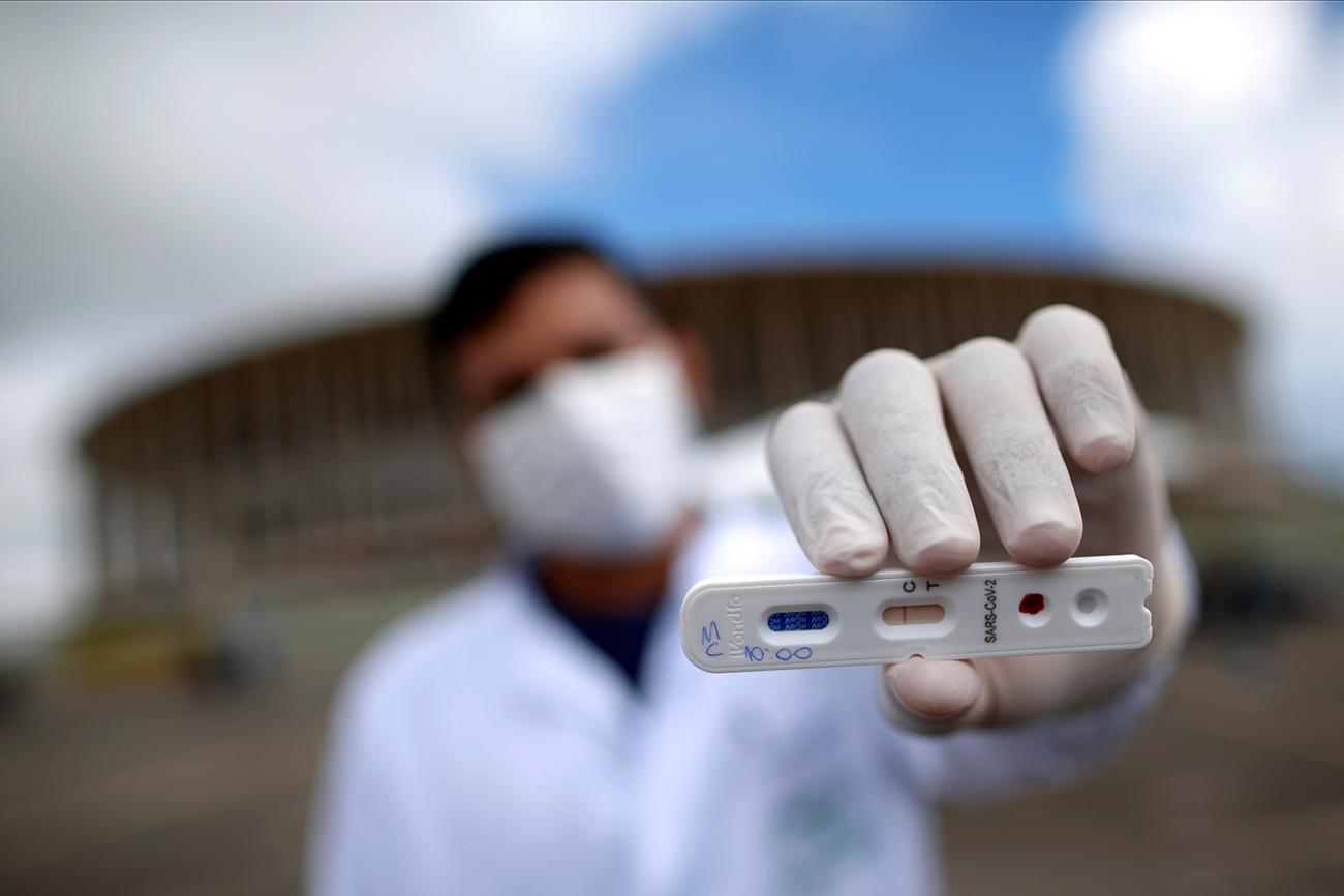 A medical professional shows a negative test for novel coronavirus in front of Mane Garrincha Stadium, amid the coronavirus disease (COVID-19) outbreak, in Brasilia, Brazil, on April 21, 2020. The photo shows a health worker holding a test at the camera with a stadium in the background. the photographer is using a telephoto/macro lens so that everything is blurred out in the shot, including the man, with the exception of the small plastic cassette-like test.  REUTERS/Ueslei Marcelino