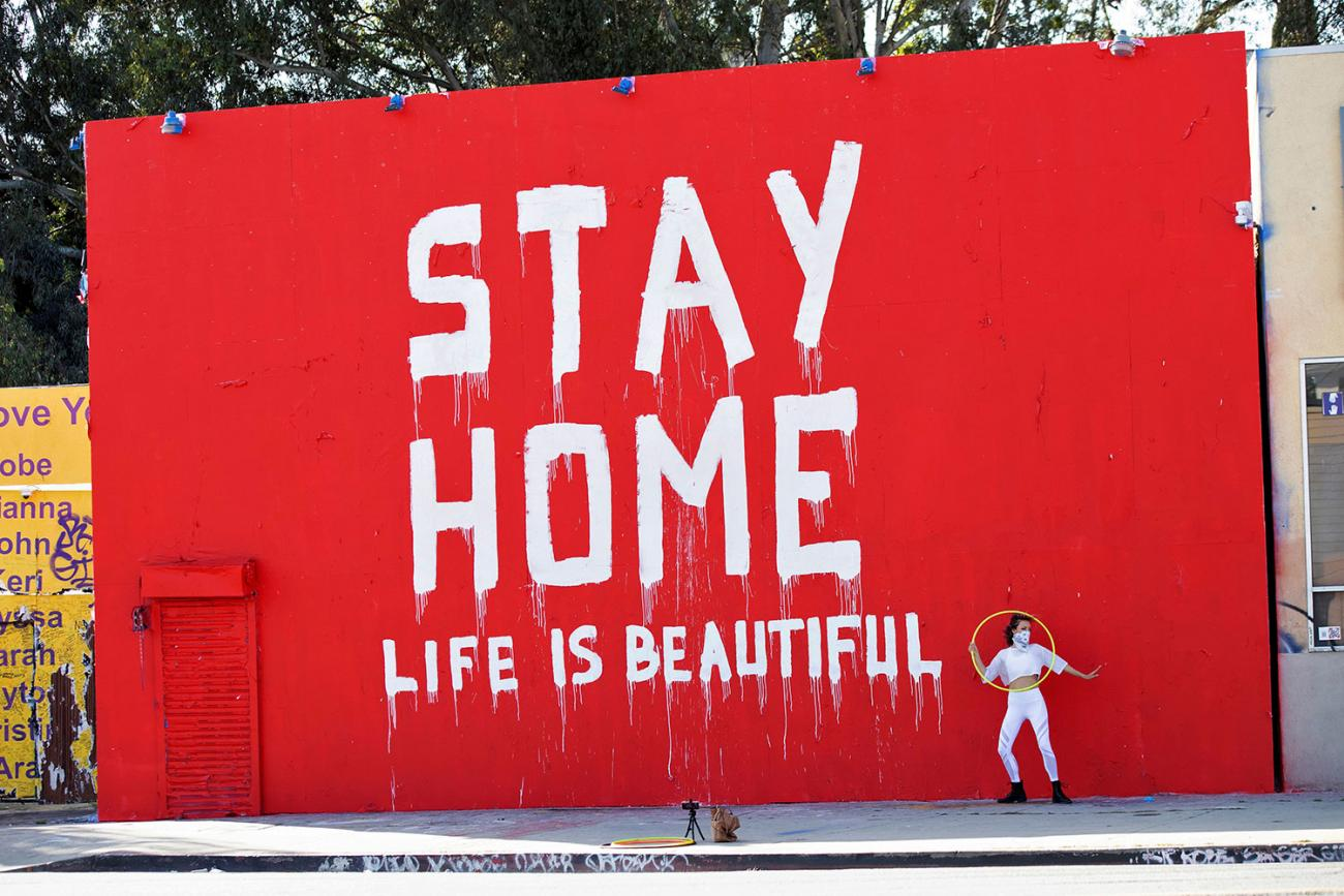 """Dance instructor Morgan Jenkins makes a video in Los Angeles, California in front of a mural during the coronavirus pandemic on April 3, 2020. The photo shows a huge striking but crudely hand painted sign that reads """"Stay Home / Life is Beautiful."""" REUTERS/Mario Anzuoni"""