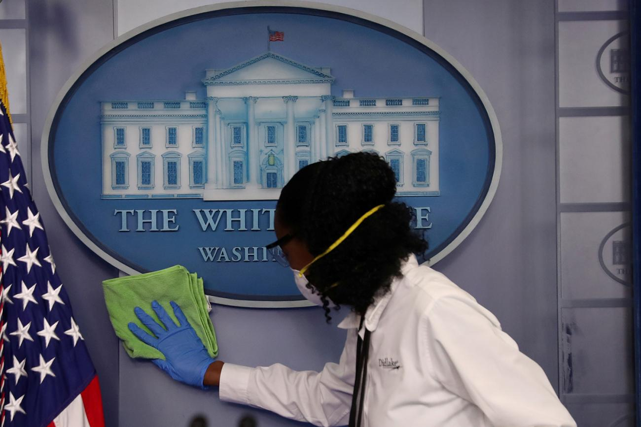 Workers clean the area around the podium before a coronavirus disease (COVID-19) outbreak task force press conference in the briefing room at the White House in Washington, D.C. on April 13, 2020. This is a striking image for its subject matter. It's a shot of the podium we don't normally see—empty of politicians and instead a worker in protective gear is cleaning the White House emblem. REUTERS/Leah Millis