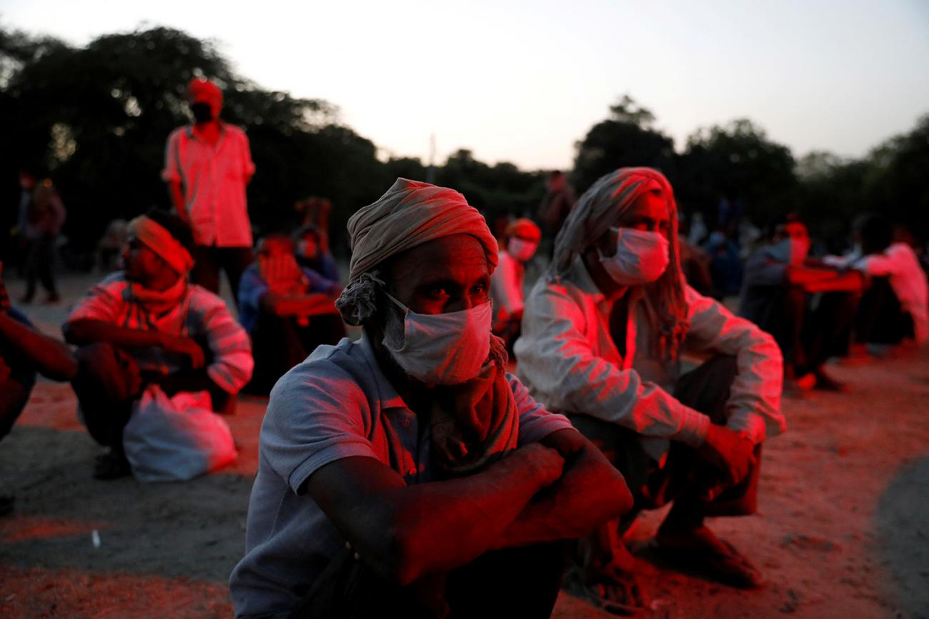 Migrant workers and homeless people wait on the banks of Yamuna river in Delhi on April 15, 2020, as police arrange buses to transfer them to shelters after India extended a nationwide lockdown. This is an eerie and haunting photo with several people sitting on the ground in an outdoor location in low lighting. They are bathed in a dark red light. REUTERS/Anushree Fadnavis