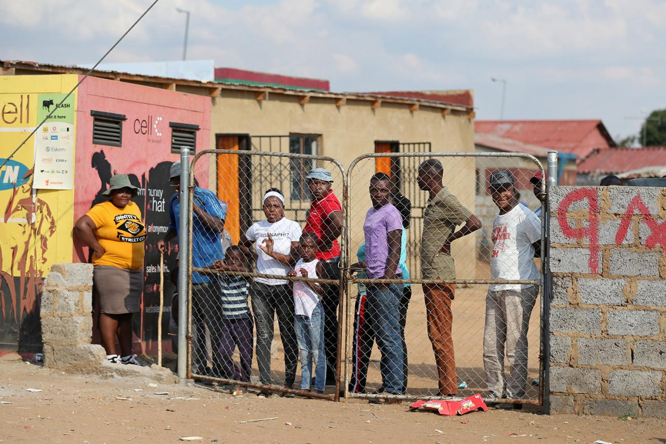 Residents look from behind a closed gate as members of the military patrol during a nationwide lockdown aimed at limiting the spread of novel coronavirus—in Soweto, South Africa on April 23, 2020. The photo shows several people congregated behind a closed fence though there is a very large gap between the fence and the adjacent wall. REUTERS/Siphiwe Sibeko