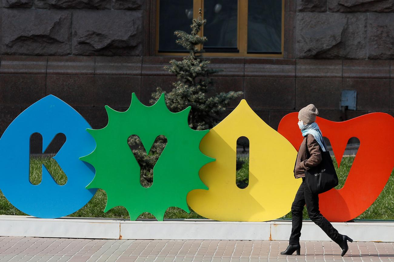 A woman wearing a mask during the coronavirus pandemic walks along the empty main street Khreshchatyk in central Kyiv, Ukraine on March 30, 2020—a colorful sign behind her bears the name of the city. This is a striking photo with a stylish woman walking in front of a sign with the city's name. REUTERS/Gleb Garanich