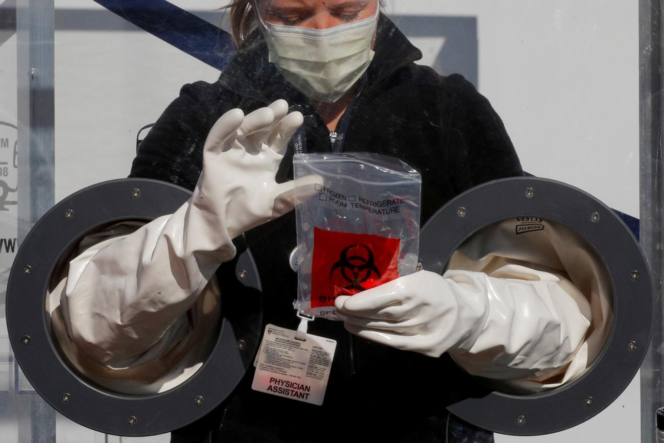 Physician Assistant Cori Kostick demonstrates a booth used to administer tests for coronavirus at the Brigham and Women Hospital in Boston, Massachusetts, on May 5, 2020. The photo shows the worker behind a protective barrier with incorporated gloves, allowing her to work with patients on the other side. REUTERS/Brian Snyder