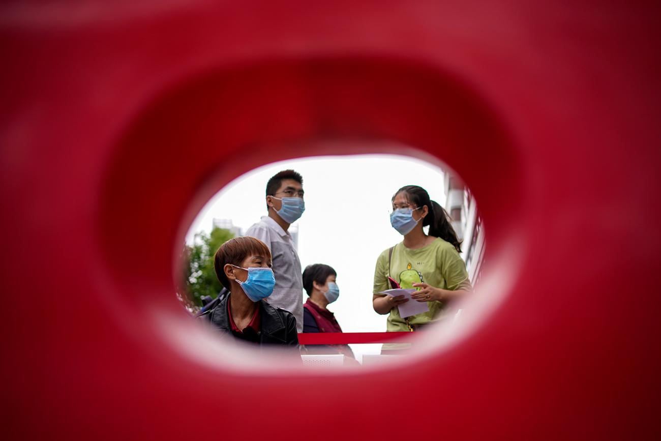 Residents wearing face masks queue for nucleic acid testings in Wuhan, the Chinese city hit hardest by the coronavirus disease (COVID-19) outbreak, Hubei province, China May 16, 2020. The photo shows what appears to be a family through the hole of a plastic barricade. REUTERS/Aly Song