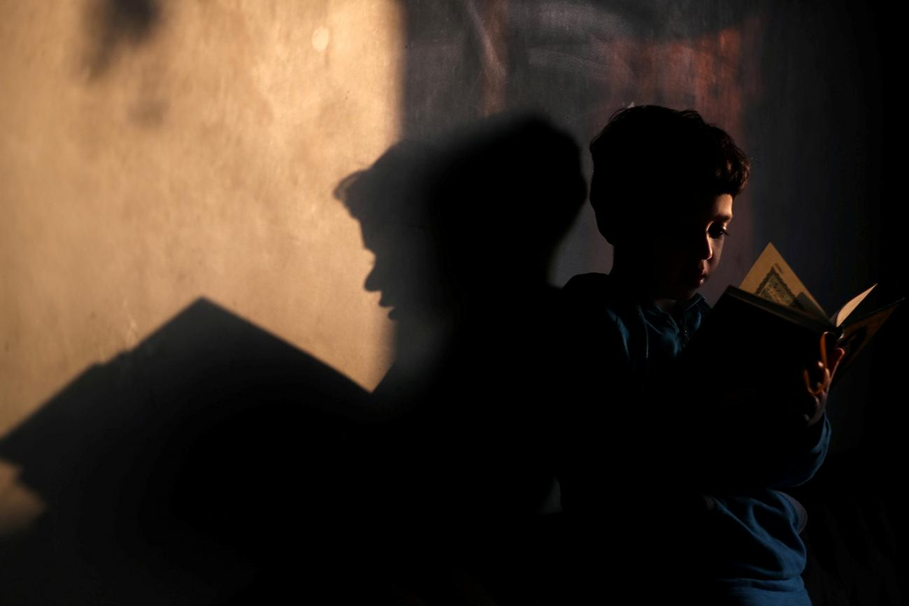 A boy reads the Koran after morning prayers with his family during the holy month of Ramadan, as Egypt ramps up efforts to slow the spread of the coronavirus in Cairo, Egypt, on April 26, 2020. Picture shows the boy reading with his shadow cast on the wall behind him. REUTERS/Mohamed Abd El Ghany