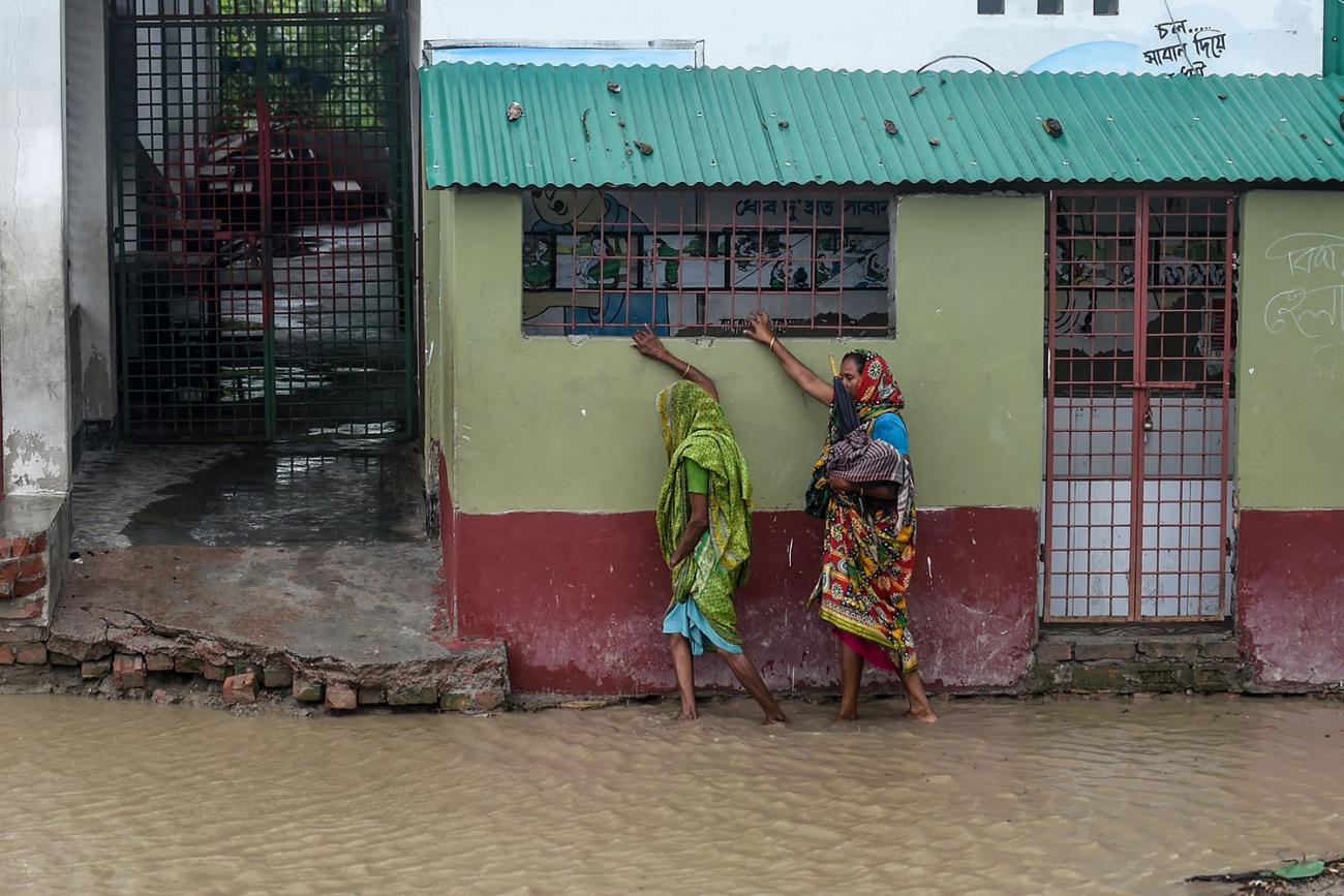 """Residents walk along a house on a flooded street heading to a shelter ahead of the expected landfall of the """"super cyclone"""" Amphan, in the Dacope of Khulna district, Bangladesh, on May 20, 2020. Photo shows two people walking and hanging on to a building as they navigate the flooded streets. AFP/Munir uz Zaman via Getty Images"""