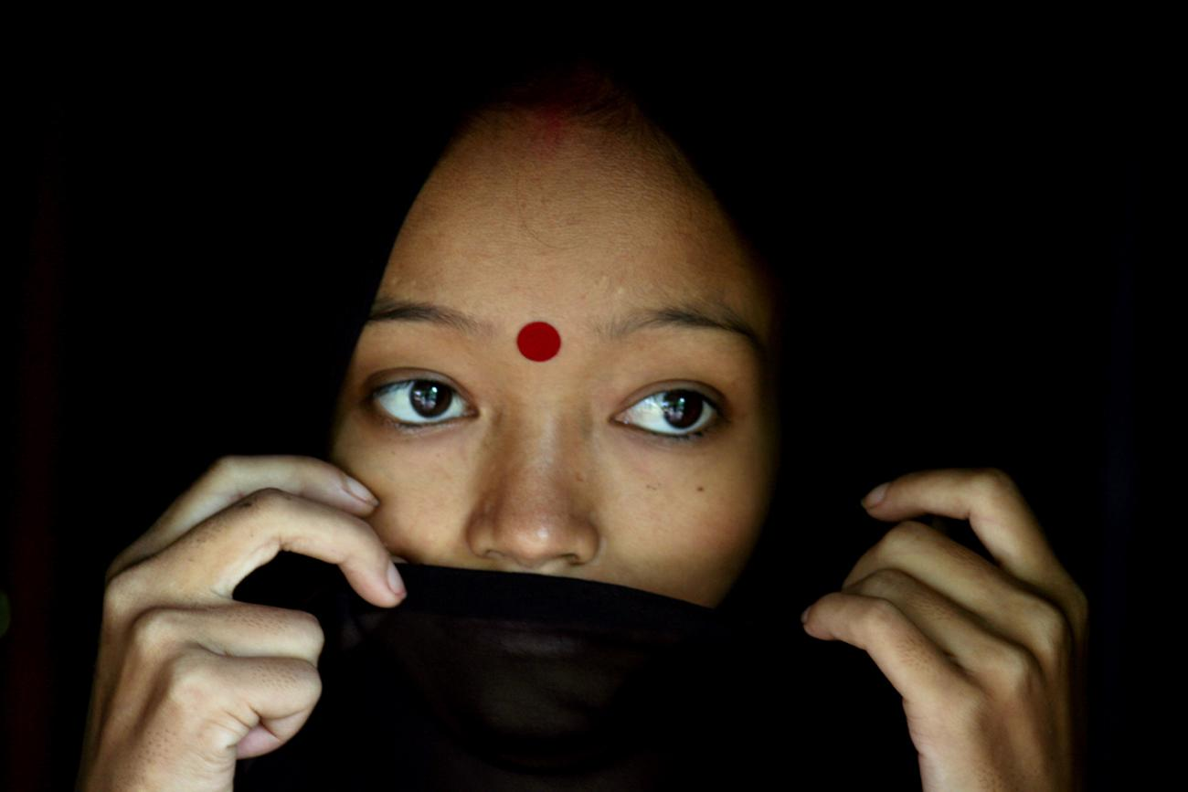 A woman living with HIV/AIDS stands in her hut in the northeastern Indian city of Siliguri on July 23, 2005. The photo shows the woman with a wrap covering her mouth. REUTERS/Rupak De Chowdhuri