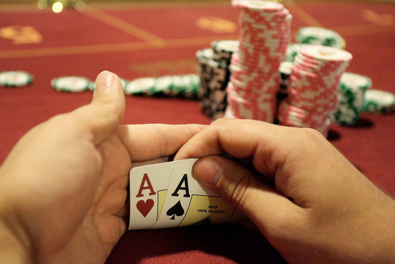 A player checks his cards during the finals of the Russian Masters Poker Cup at the Azov-City, Russia, gambling zone, south of Russia's southern city of Rostov-on-Don, on September 23, 2010. Photo shows a pair of hands holding up the corners of two cards to reveal a pair of aces. A large stack of chips is in the background. REUTERS/Vladimir Konstantinov
