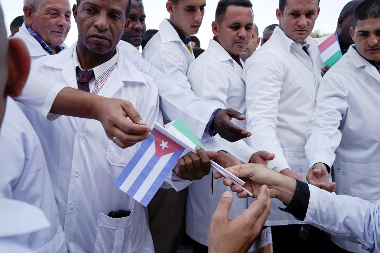 Cuban doctors receive Cuban and Italian flags during a farewell ceremony before departing to Italy to assist, amid concerns about the spread of the coronavirus in Havana, Cuba, on March 21, 2020. the photo shows doctors lined up taking flags of Italy and cuba. REUTERS/Alexandre Meneghini