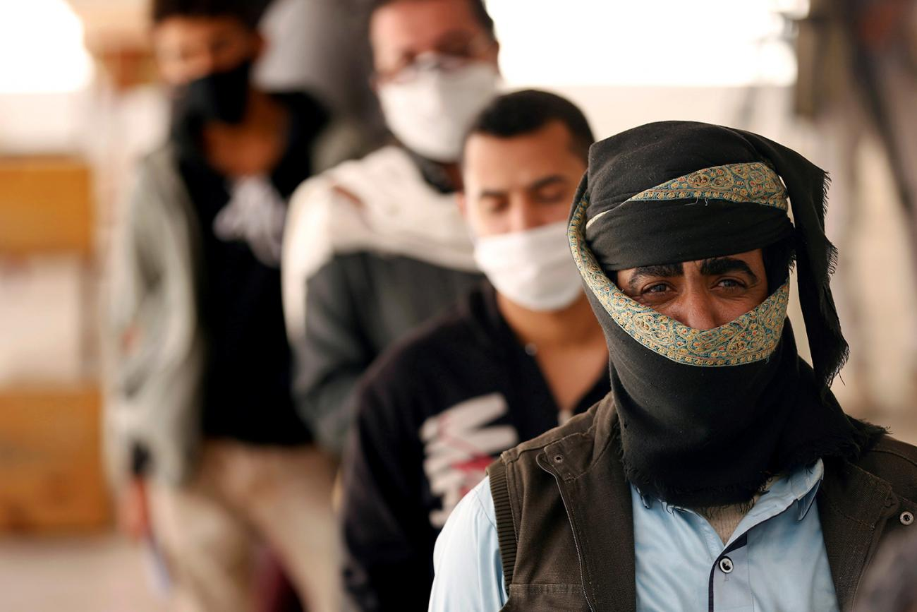 People stand in line to receive vouchers at a food distribution center supported by the World Food Program in Sanaa, Yemen, on June 3, 2020 amid the coronavirus pandemic. The photo shows several men lined up in a queue. They are all wearing facemasks. REUTERS/Khaled Abdullah