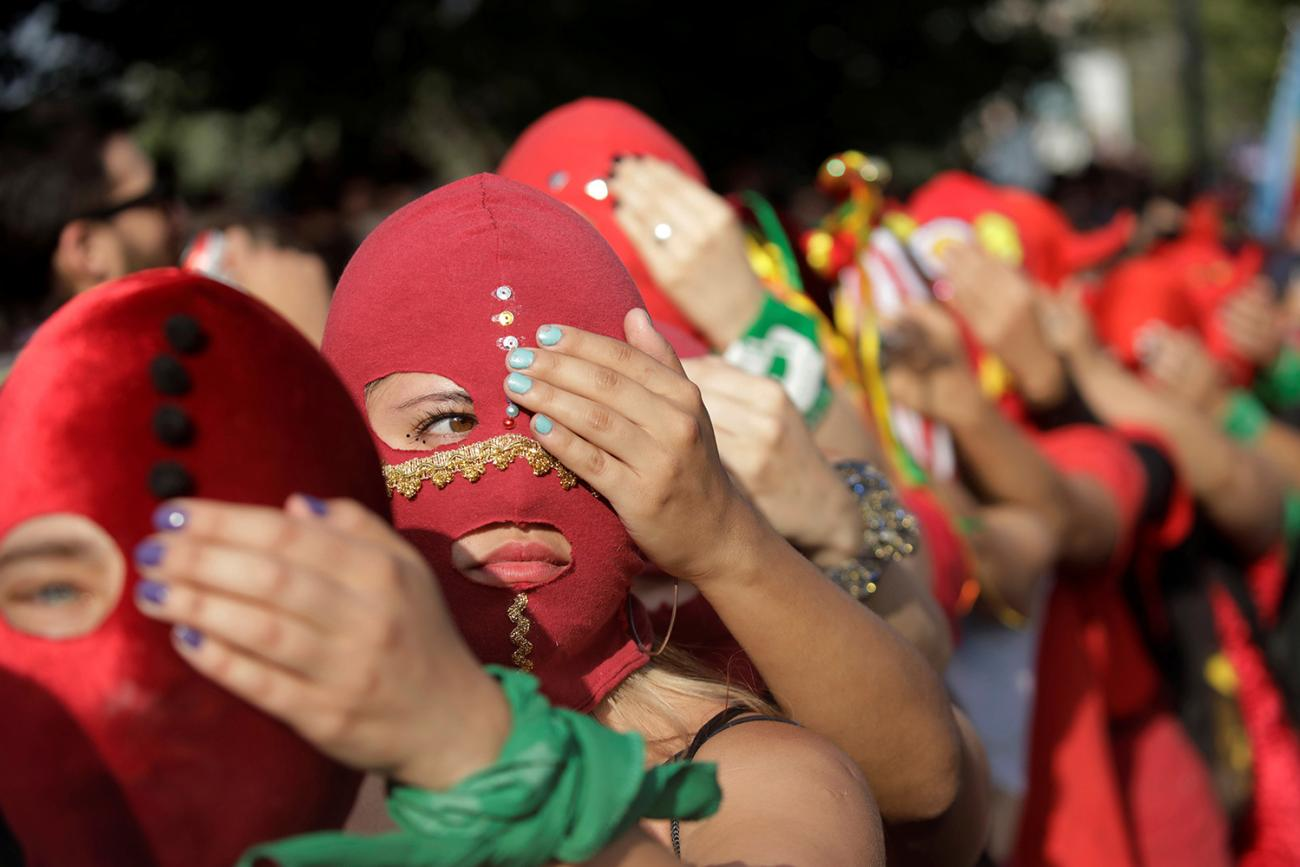 """""""We cannot afford to unsee domestic abuse after COVID-19,"""" the authors write. Here women wearing masks take part in a protest against gender violence in Santiago, Chile, on December 6, 2019. The photo is a striking image of women wearing red masks lined up, each person holding a hand over one eye of the person in front of them. REUTERS/Andres Martinez Casares"""